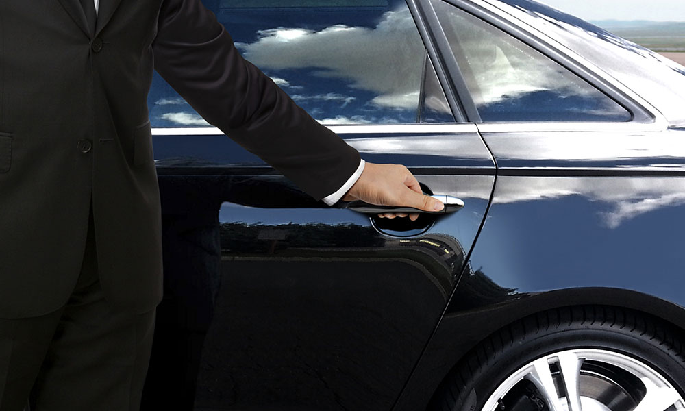 Chauffer holding door handle on luxury car