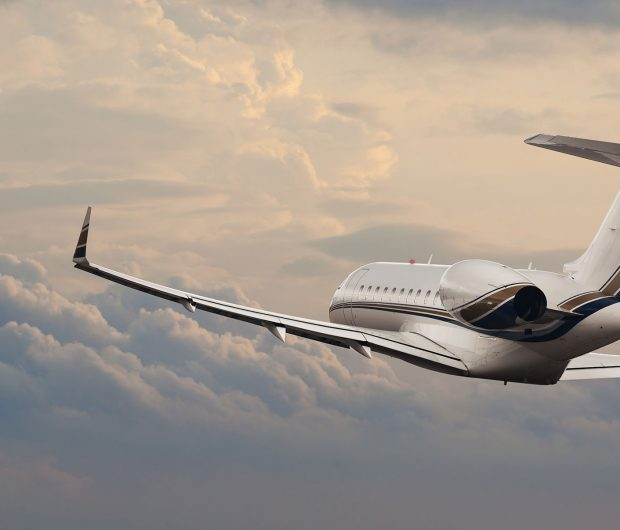 White private jet with brown and black stripe flying in overcast sky